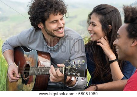 Young Man Looking At Woman While Playing Guitar Outdoor