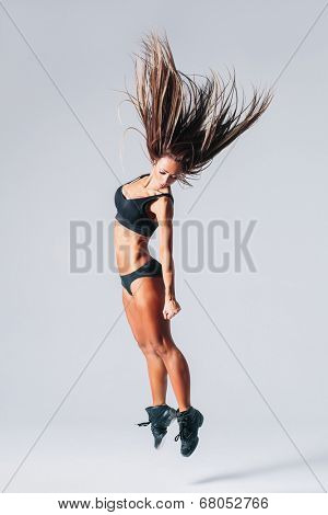 young beautiful dancer posing on studio black background