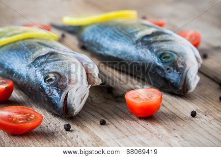 Two Raw Seabass Fish With Cherry Tomatoes On A Rustic Wooden Background