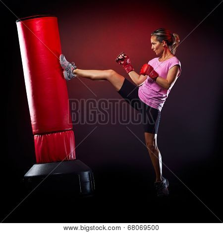 young woman exercising bag boxing in studio