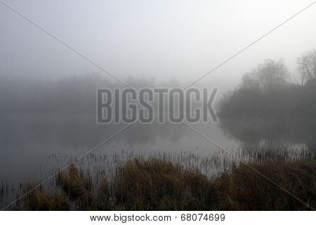 A foggy lake shrouded in autumnal mist.