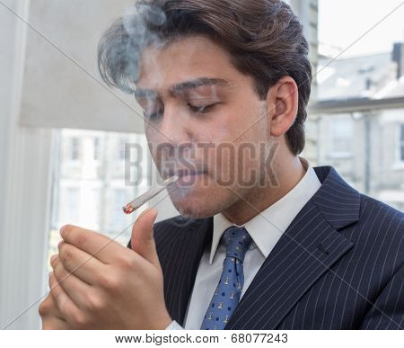 Young Businessman Lighting Up A Cigarette