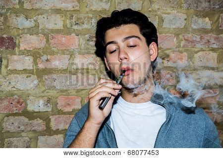 Young Man Contentedly Puffing On An E-cigarette