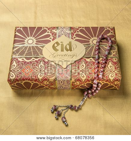 A tag with 'Eid Mubarak' message in english on a golden gift box along with islamic prayer beads