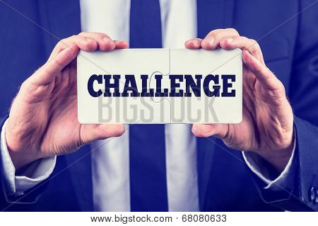 Man Holding Up Two Puzzle Pieces With Challenge