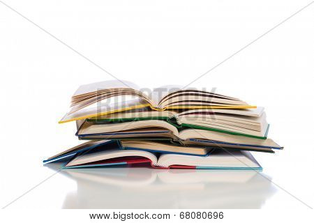 A stack of opened textbooks on a white background