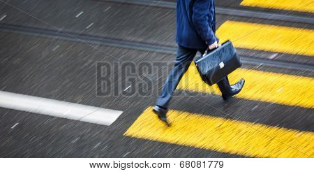 Man rushing over a road crossing in a city on a rainy day (motion blurred image)