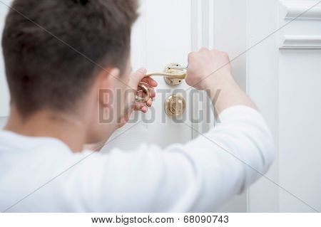 Young man fixing the door handle