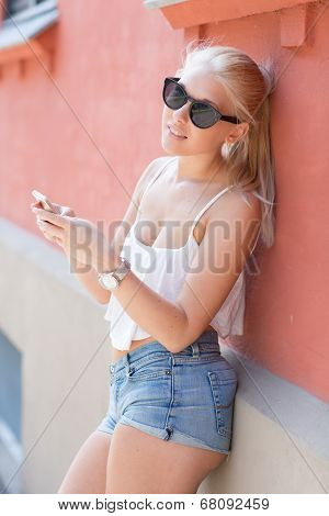 Attractive blonde teenage girl using smartphone