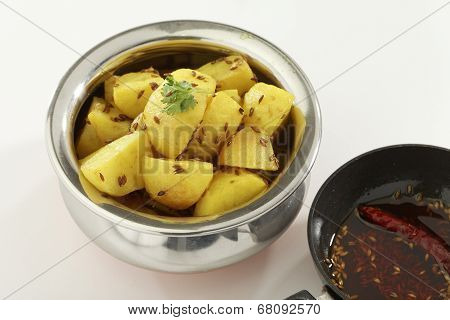 Indian Food: Fried potato in steel pot with cumin red chilly in oil used.