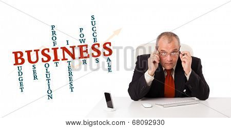 businesman sitting at desk with business word cloud, isolated on white