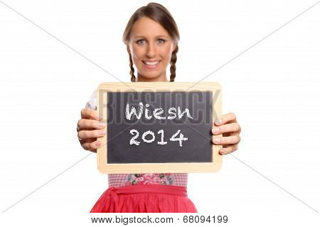 Young woman in a dirndl holding a slate