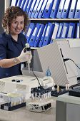 Scientist, pathologist, chemist or other lab worker takes a sample  poster