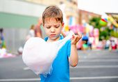 foto of candy cotton  - Portrait of cute child eating cotton candy over a summer fair festival background - JPG