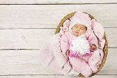 picture of gift basket  - Baby girl with gift sleeping on wooden background newborn in basket with present - JPG