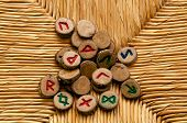 stock photo of rune  - Looking own on a pile of germanic runes an ancient alphabet known as the futhark on a woven rattan surface - JPG