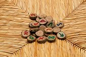 stock photo of rune  - A pile of germanic runes an ancient alphabet known as the futhark are on a woven rattan surface - JPG