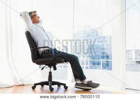 Smiling man with glasses sitting on office chair and relaxing at apartment