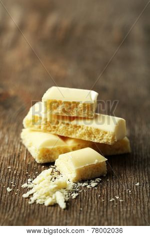 Tasty white porous chocolate on wooden table, close up