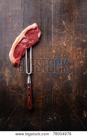 Raw Fresh Meat Striploin Steak On Meat Fork On Dark Wooden Background