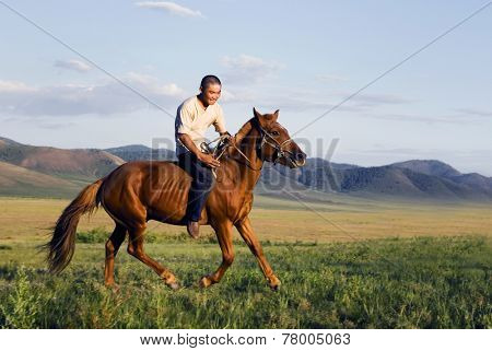Young man riding a horse in a scenic view of nature.