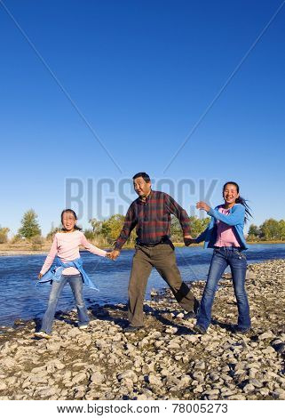 Mongolian family anjoy walking by the river.