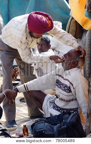 Sikh dentist treats teeth of old man without during traditional camel fair holiday at Pushkar,India