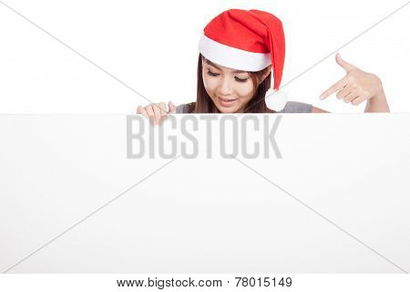 Asian Girl With Red Santa Hat Look Down And Point  To A Blank Sign