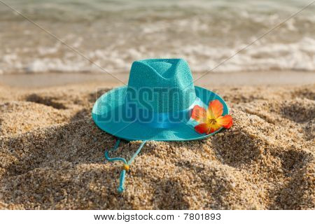 Turquoise Summer Hat And Flower On The Beach