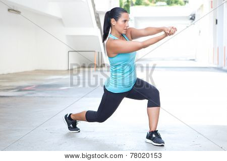 Beautiful hispanic sport woman demonstrating tai chi stance with pretend sword, outdoor. Concept of healthy lifestyle.
