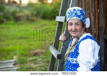 Old woman posing at village in folk costume. Picture with space for text.