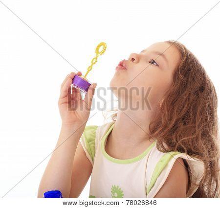 Beautiful little girl blow bubbles.