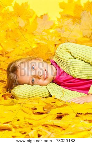 Little blond girl lays on the autumn yellow leaves