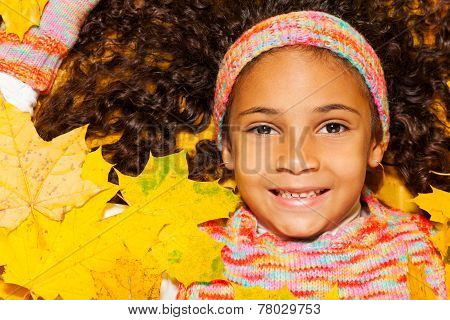 African girl with curly hair in orange leaves