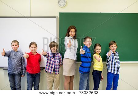 education, elementary, gesture and people concept - group of school kids and teacher showing thumbs up in classroom