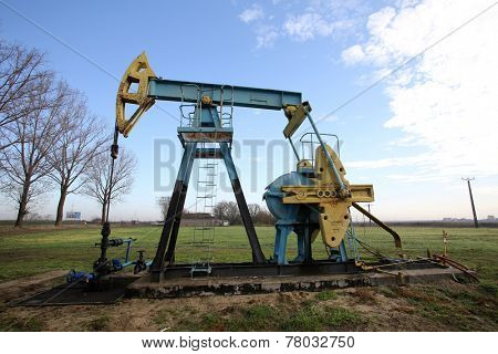 ARAD, ROMANIA - FRIDAY, DECEMBER 5, 2014: A pumpjack pumps oil out of the ground at a production field operated by OMV Petrom S.A, the largest gas and oil producer in Eastern Europe