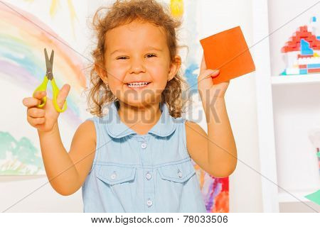 Smiling little girl with scissors and square