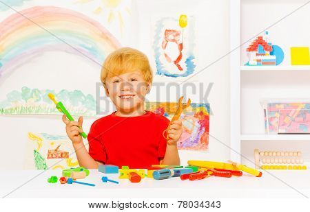 Cute preschool blond boy with toy work tools