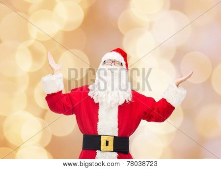 christmas, holidays and people concept - man in costume of santa claus with raised hands over beige lights background