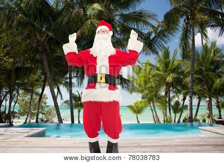 christmas, holidays, travel and people concept - man in costume of santa claus having fun over swimming pool on tropical beach background