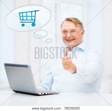 technology, people, oldness, gesture and online shopping concept - old man in eyeglasses with laptop computer at home showing thumbs up and text bubble with trolley