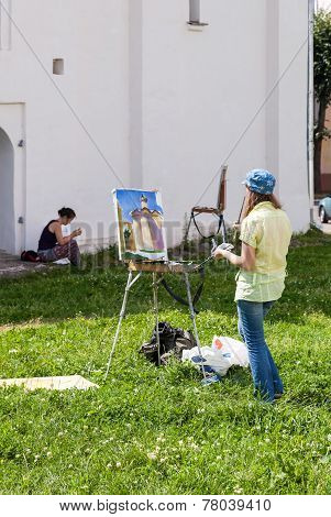 Young Artists Paint At The Walls Of An Ancient Cathedral