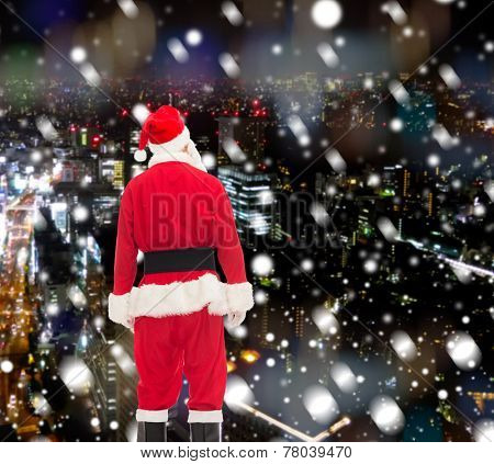 christmas, holidays and people concept - man in costume of santa claus from back over snowy night city background