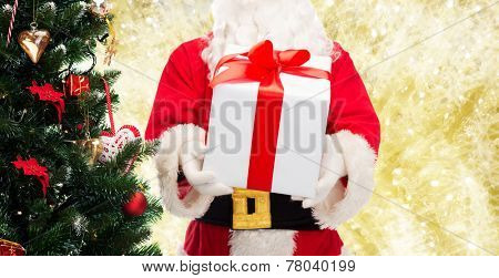 christmas, holidays and people concept - close up of santa claus with gift box and tree over yellow lights background