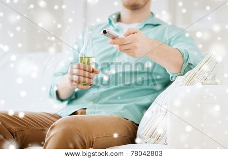 drinks, television, leisure and people concept - man changing tv channels and drinking beer at home