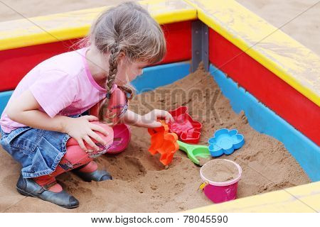Beautiful Cute Little Girl Playing In Sandbox On Warm Sunny Day