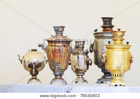 Five Russian Samovars Of Different Shapes And Sizes Are On Table With Blue Tablecloth