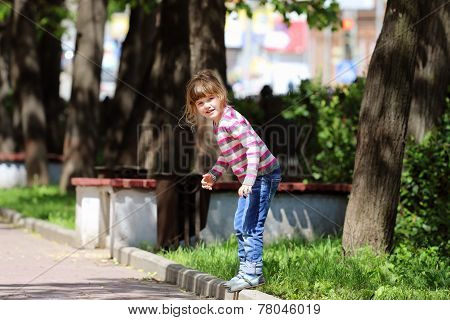 Girl In Striped Sweater And Jeans Standing On Curb On Sunny Day