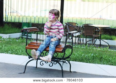 Happy Little Girl With Pictured Purple Butterfly On Face Sits On Bench