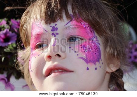 Happy Little Girl With Pictured Purple Butterfly On Face With Tinsel